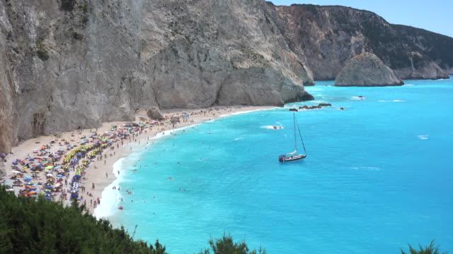 vídeos y material grabado en eventos de stock de playa con turistas y barco anclado en la playa - anclado