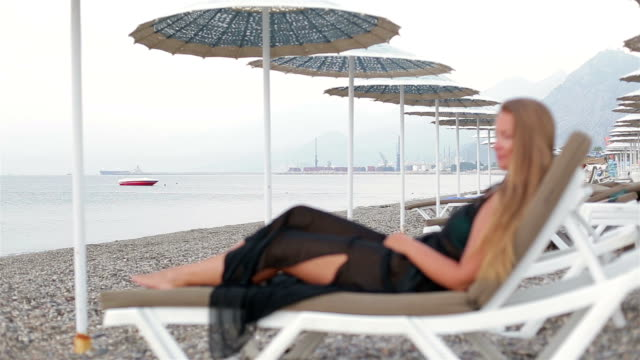 Beach woman enjoying the sea lying on the sun loungeron in the beach video