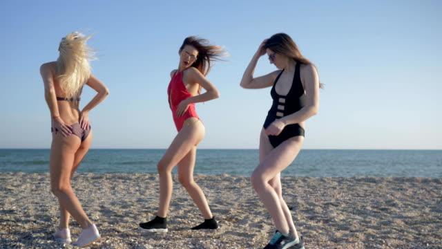 vídeos de stock, filmes e b-roll de juventude de praia, companhia de dança de mulheres em trajes de banho e óculos de sol se divertir na orla marítima - amizade feminina