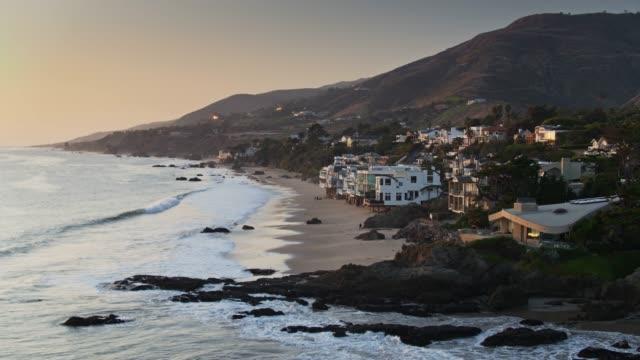 vídeos de stock e filmes b-roll de beachfront houses in malibu at sunset - aerial view - estrada 001