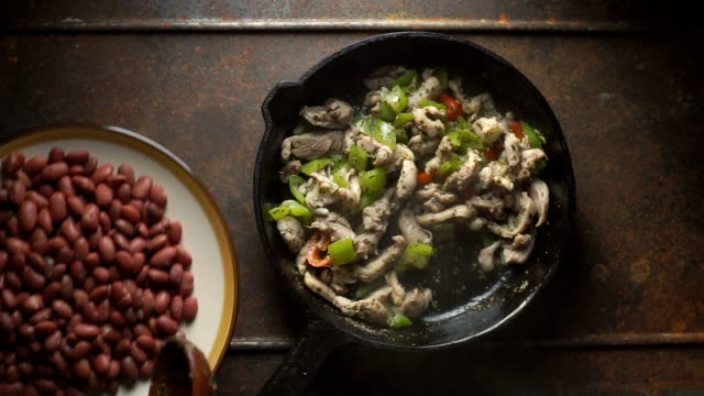 Beans are spread in a frying pan with pepper and chicken. Video video