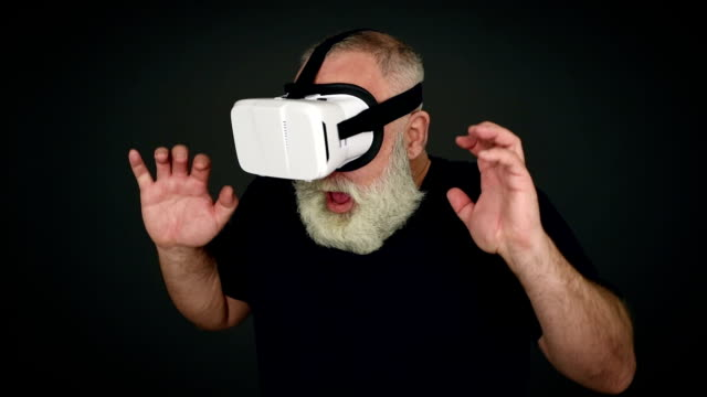 Beard Elderly man frightened in virtual reality glasses on a black background video