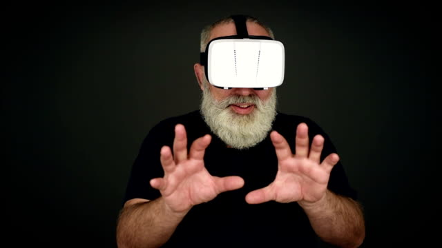 Beard Elderly man scared in virtual reality glasses on a black background video