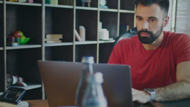 Beard man working laptop computer in home office. Man looking laptop screen