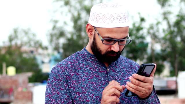Beard Muslim men using touch screen mobile phone outdoors video