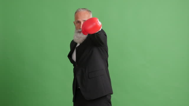 Bearded adult businessman strikes against a green background video