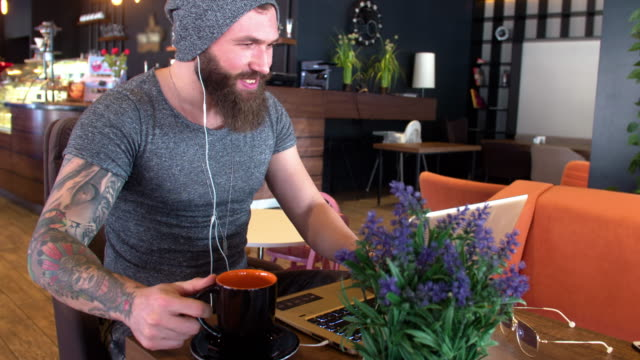Bearded and tattooed hipster chatting on his laptop in the cafe video