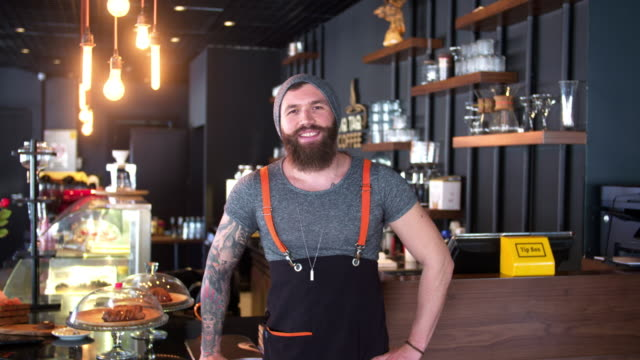 Bearded and tattooed hipster coffee shop owner posing video