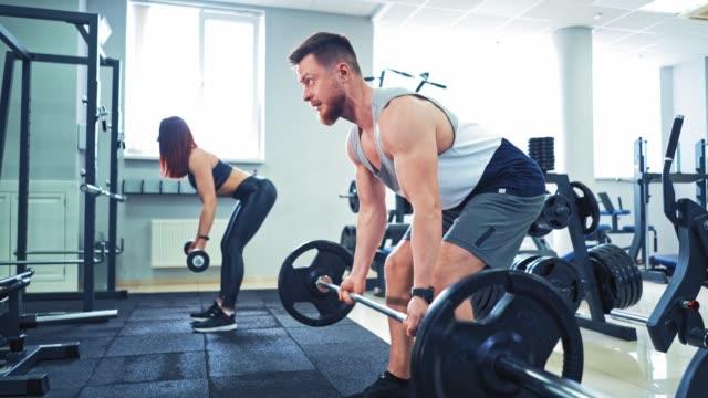수염이 있는 운동 선수와 건강한 여성이 스포츠 센터에서 무거운 바벨을 들어 올리고 있습니다. - 잘생김 스톡 비디오 및 b-롤 화면