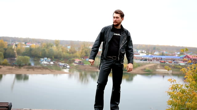 bearded biker rejoicing on the wall in black leather jackets - топ модель стоковые видео и кадры b-roll