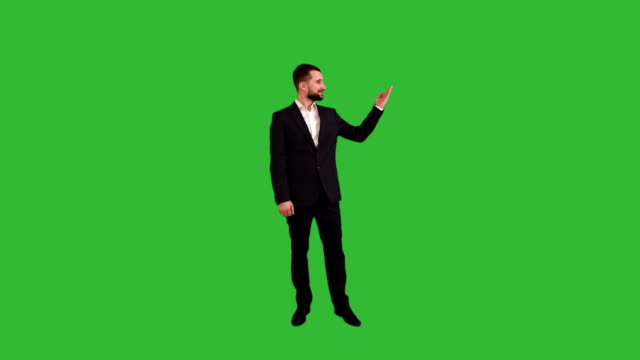 bearded businessman showing a copy space  on a green background video