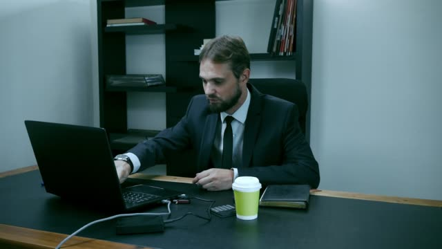 bearded businessman sitting in the office at the laptop, male outraged, slow motion - ассистент стоковые видео и кадры b-roll