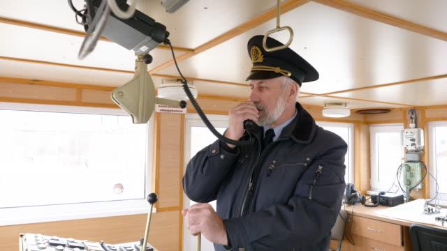 船長橋にラジオを設定する船のひげを生やした船長。ナビゲーションオフィサーは、現代の船でナビゲーションパネルとダッシュボード上のデバイスを管理します。セーリングと出荷の概念� - デッキ点の映像素材/bロール