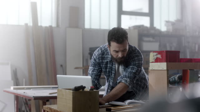 bearded carpenter researching on internet using laptop on working table at workshop - owner laptop smartphone video stock e b–roll