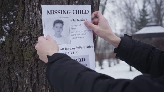skäggig kaukasisk man hängande försvunnen pojke annons på trädet. ung far söker efter sin förlorade son. kidnappning, förtvivlan, sociala problem. - saknad känsla bildbanksvideor och videomaterial från bakom kulisserna