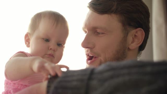vídeos de stock, filmes e b-roll de barbudo pai beijar o bebê. conceito de tempo de pai. bebê tocando o relógio de pulso - punho