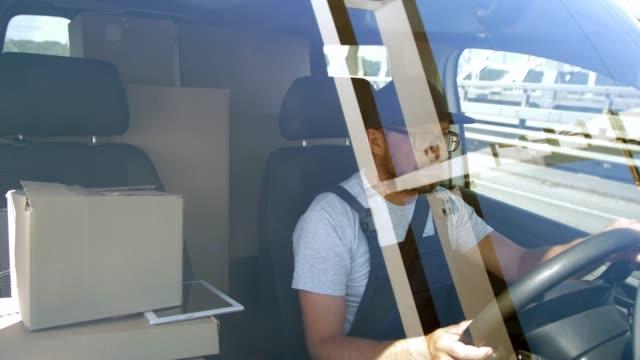 bärtigen liefermann fährt auto über stadtbrücke - van stock-videos und b-roll-filmmaterial