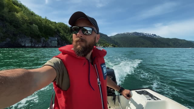 Bearded fisherman on a small fishing boat: selfie in a fjord in Norway