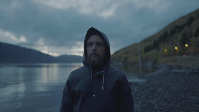vídeos y material grabado en eventos de stock de retrato de pescador barbudo: con impermeable junto a un fiordo por la noche - bergen