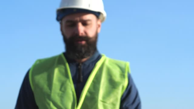 bearded foreman in yellow helmets and vests inspect the construction site. port worker video