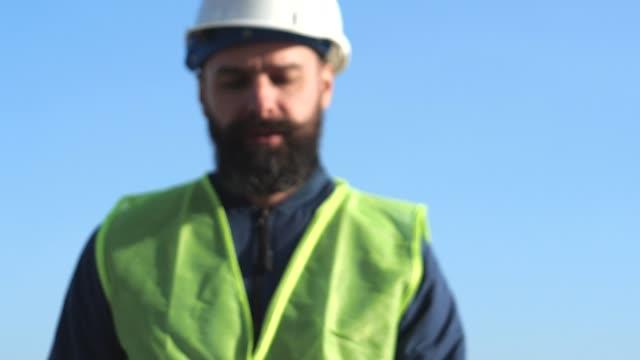 capatano barbudo em capacetes amarelos e coletes inspecionam o canteiro de obras. trabalhador portuário - vídeo