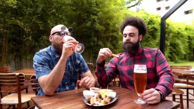 Bearded friends enjoying chicken wings and beer at a restaurant