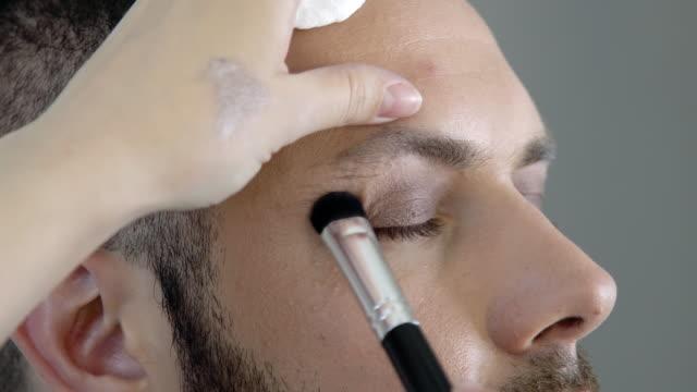 stockvideo's en b-roll-footage met bebaarde homo of metroseksuele man die make-up krijgt - vetschmink