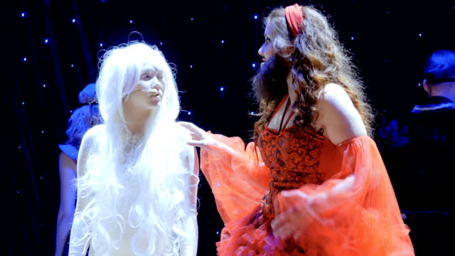 stockvideo's en b-roll-footage met bebaarde meisje zingt lied aan albino meisje op het podium in theater - vetschmink