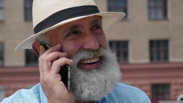 bearded gray-haired man speaks by phone - 50 54 lata filmów i materiałów b-roll
