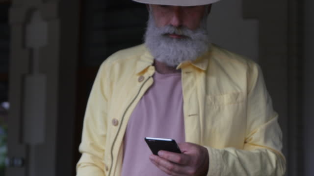 a bearded gray-haired man writes a message on a smartphone and drinks coffee in a cafe - 50 54 lata filmów i materiałów b-roll