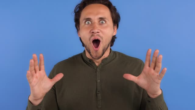 bearded guy in khaki colored shirt. he looking surprised or shocked and saying wow, while posing against blue studio background. close up - {{relatedsearchurl(carousel.phrase)}} video stock e b–roll