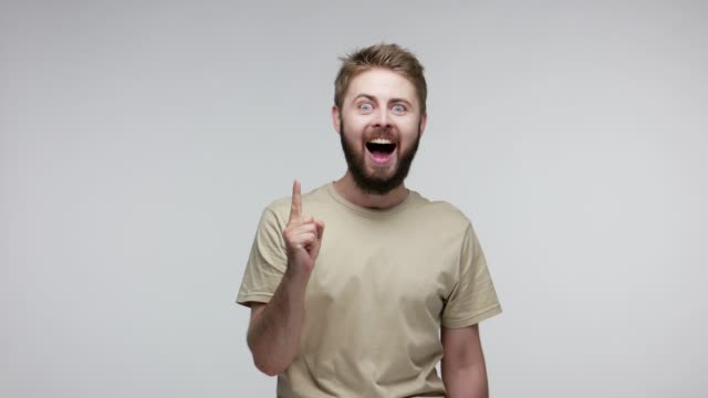 Bearded guy shouting for joy and raising finger with great idea gesture, amazed surprised by suddenly found answer