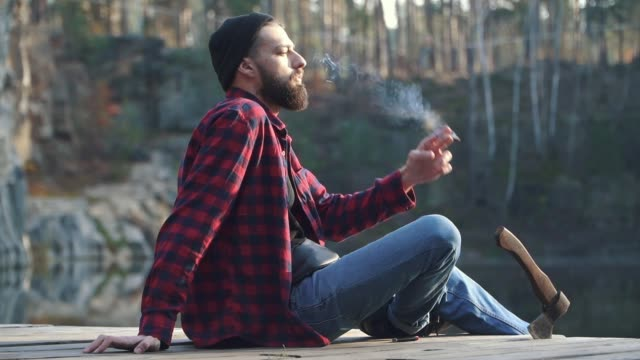 bearded guy sit in the forest near river and smoking brown cigar. brutal serious man with a black beard in a plaid shirt and blue jeans smoking a cigar outdoors. - кепка стоковые видео и кадры b-roll
