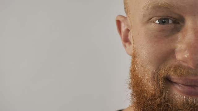stockvideo's en b-roll-footage met een bebaarde man glimlacht in de camera zeer close-up. - portrait background