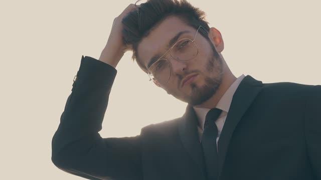 明るい日光スローモーションでネクタイポーズを持つひげを生やした男 - スタイリッシュ点の映像素材/bロール