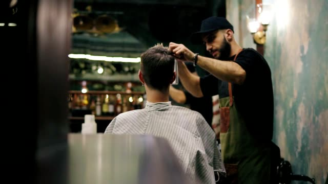 Bearded hairdresser spraying water and combing wet hair of his male client in a retro stylish barbershop. Male hairstyle. Slowmotion shot video