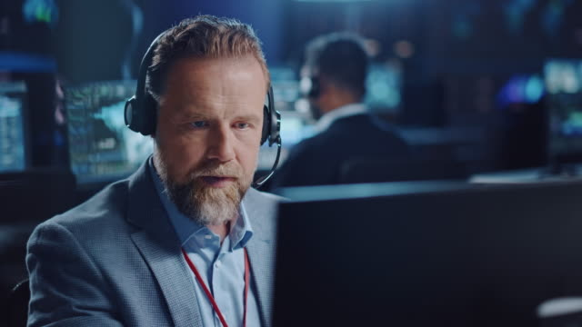 bearded happy senior technical support specialist is talking on a headset while working on a computer in a dark monitoring and control room filled with computer display screens and data servers. - call center стоковые видео и кадры b-roll