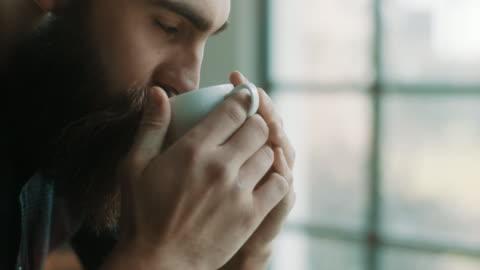 vídeos de stock e filmes b-roll de bearded hipster man drinking coffee at atelier - bebida