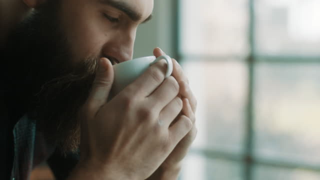 bearded hipster man drinking coffee at atelier - coffee стоковые видео и кадры b-roll