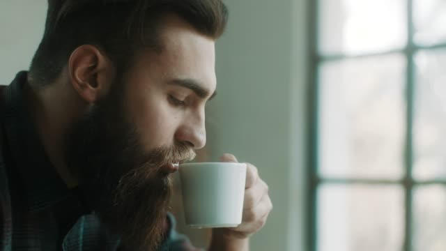 bearded hipster man drinking coffee at atelier - barba peluria del viso video stock e b–roll