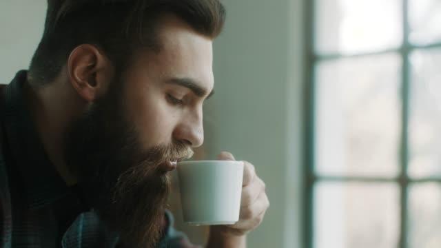 vídeos y material grabado en eventos de stock de barbudo hombre hipster tomando café en el atelier - café bebida