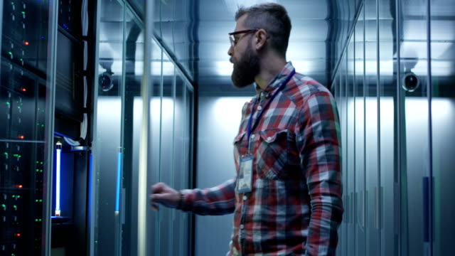 Bearded IT specialist setting servers in data center Adult bearded system administrator in glasses walks over to the server rack and opens the rack door in the server room and makes the hardware settings using a laptop. server room stock videos & royalty-free footage