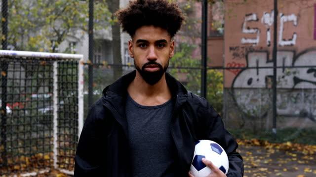 Bearded male sportsperson holding soccer ball