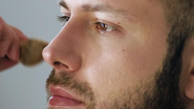 stockvideo's en b-roll-footage met bebaarde mensacteur die make-up krijgt - vetschmink