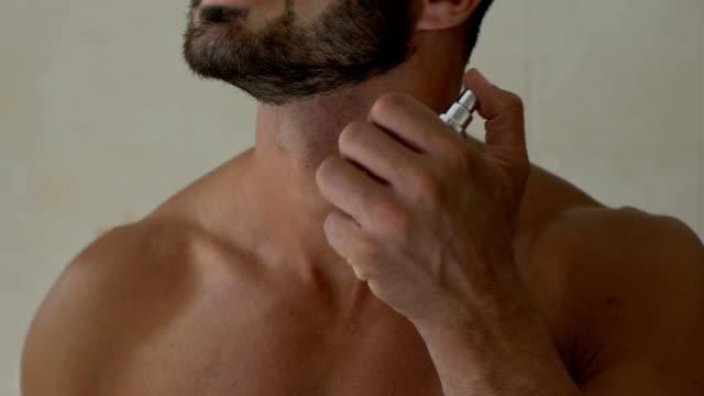 sakallı adam banyoda boyun, özel koku erkekler için parfüm uygulama - kokulu stok videoları ve detay görüntü çekimi