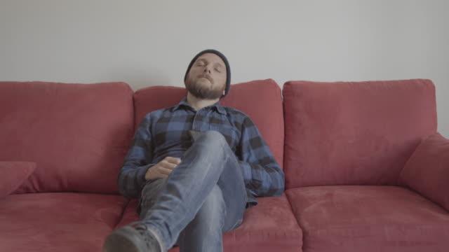 Bearded man at home on a red sofa: sleepy mood video