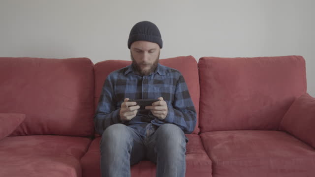 Bearded man at home on a red sofa video