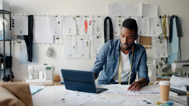 Bearded man designer drawing clothes sketching using laptop in modern studio