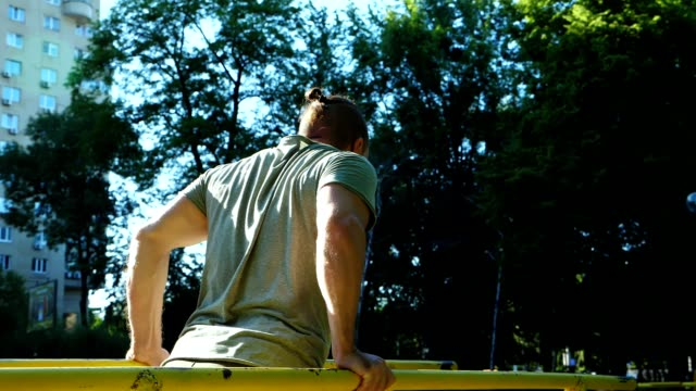 Bearded man doing push-ups on parallel bars at outdoor gym workout. Workout lifestyle concept.