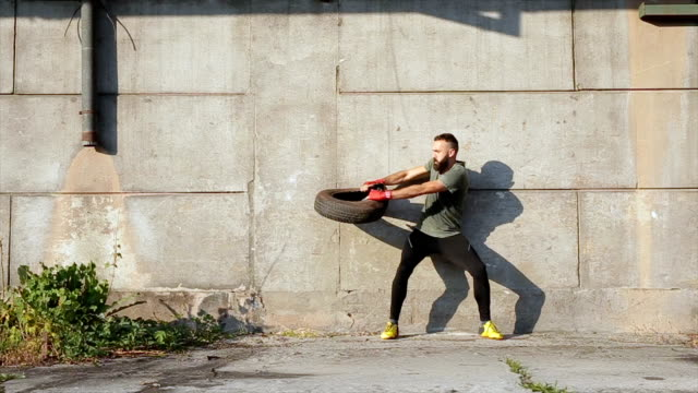 bearded man exercising with a help of a tire - man city exercise abs video stock e b–roll